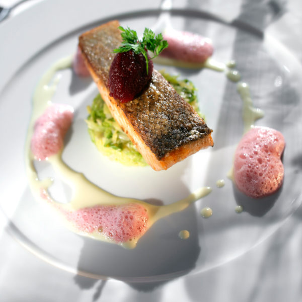Pan-Fried Salmon with foam on a round white plate